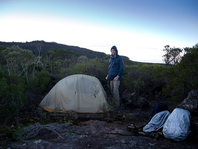 Greg at camp with the southern spur of the summit of Mt Talaterang in the distance. It was a chilly 5 degrees at 7am with the wind still blowing, however our tent and packs were nice and dry as there was no dew overnight.