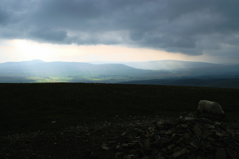 Distant Ingleborough and Whernside seen from Pen y Ghent beneath a gathering sky