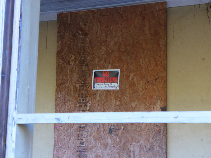 """<h1>Sign on old abandoned house</h1>The writing below the NO TRESPASSING reads, """"Property of Asbury Hills.  Smile ... you've been photographed!"""""""
