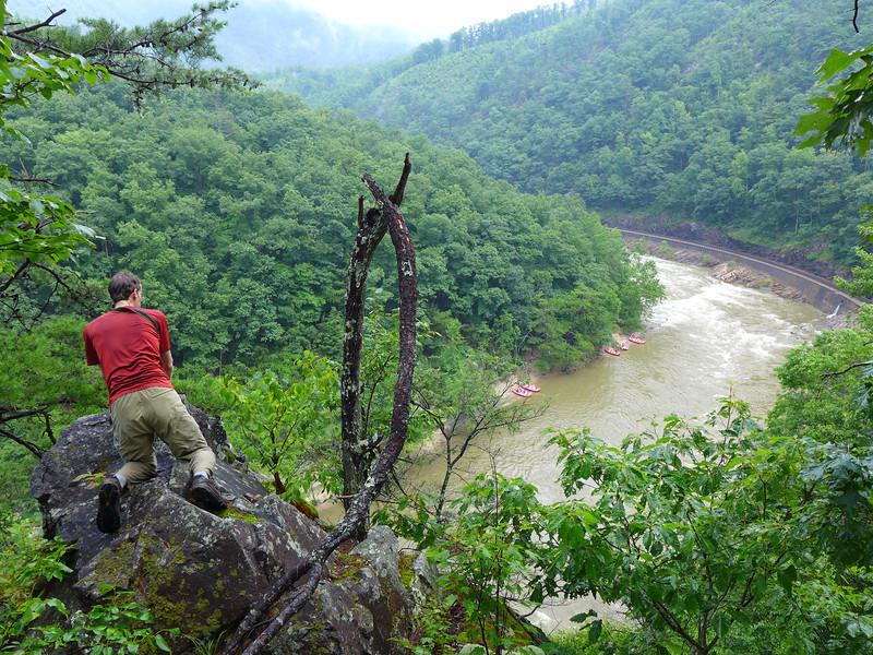 <h1>Van, looking down on the river</h1>This little knoll was so narrow that beyond that rock that Van is kneeling on there is NOTHING ... just a straight down drop to the railroad and river below.  In fact, we were almost directly above the railroad from this vantage point.