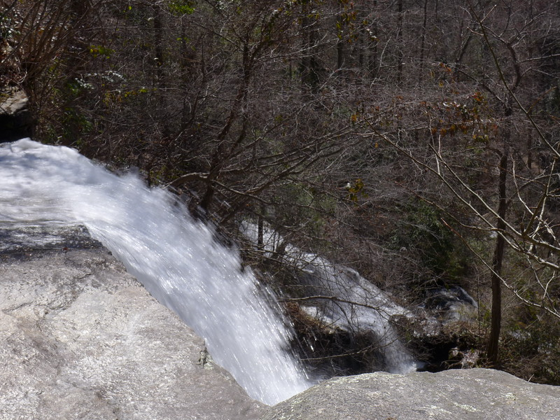 """<h1>The Main Drop</h1>From here, it's 100 feet straight down.   There's plenty of level dry rocks to safely stand (or in my case, being this close to the edge ... SIT) on, but see the next photo for where the real danger lies.  Note the """"right hand waterfall"""" in the background."""