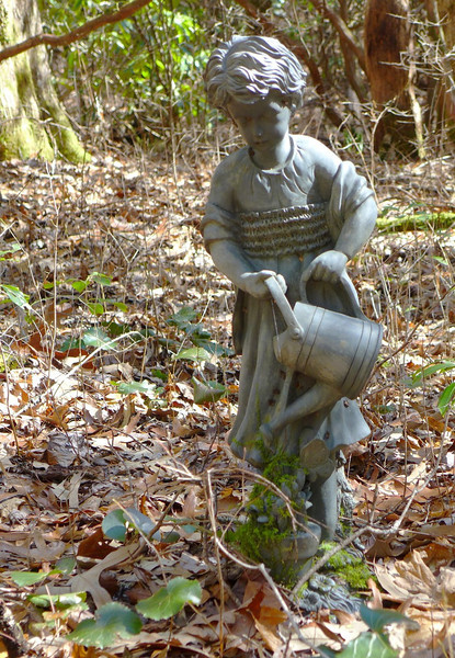 Coming up a trail after crossing a creek, my attention was first drawn to some windchimes hanging in a tree.   Below those chimes was this statue of a little girl, watering a plant.