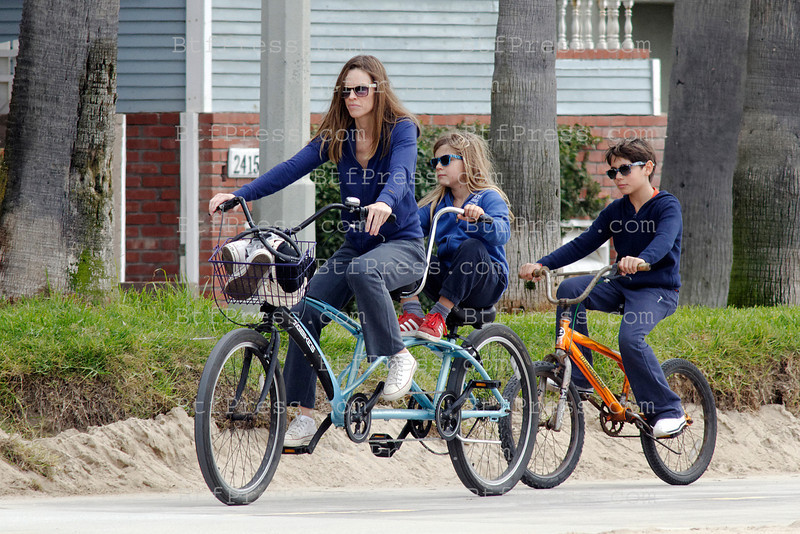 Hiary Swank rides a tandem bike with family's kids, they need to stop to fix a tecnical problem on the tandem bike, in Venice beach, California