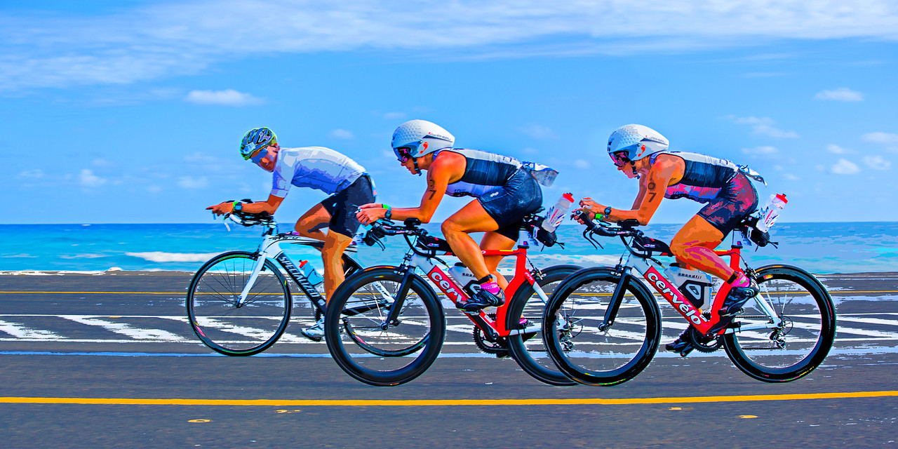 """The Overtake… Racing during the 112-mile cycling stage of Ironman Cozumel 2013 along the Playa Oriente area of Punta Morena near Mezcalitos on the east side of the island. This image is composed to ideally yield a 16"""" x 32"""" print or canvas or any other 1:2 ratio size such as 12"""" x 24""""."""
