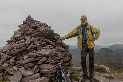 Leaning against the summit cairn of Sgurr Mhor