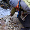 Old lady clearing a stream in Namche Bazar