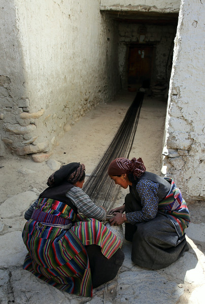 Lo Manthang weavers; this was in a side alley from a main street and the long garment being woven is the traditional colourful wrap that the ladies are wearing.