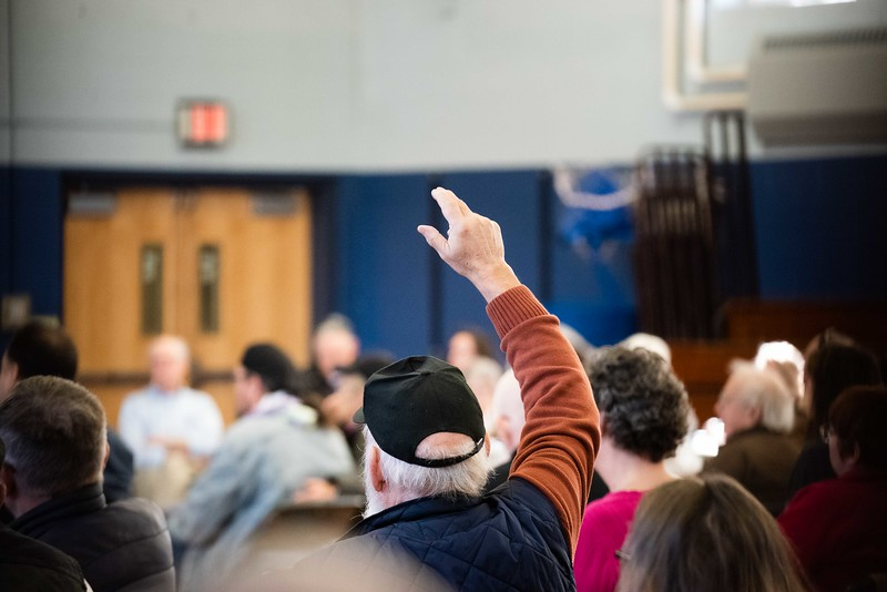 KELLY FLETCHER, REFORMER CORRESPONDENT -- Paul Barnard rasises his hand with a question pertaining to the possible relocation of the Hinsdale Fire Station during town meeting on Saturday.