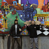 Shadd and Dan in front of a mural in Hallidie Plaza at the Powell Street Station (Mural by the Meridian Gallery)