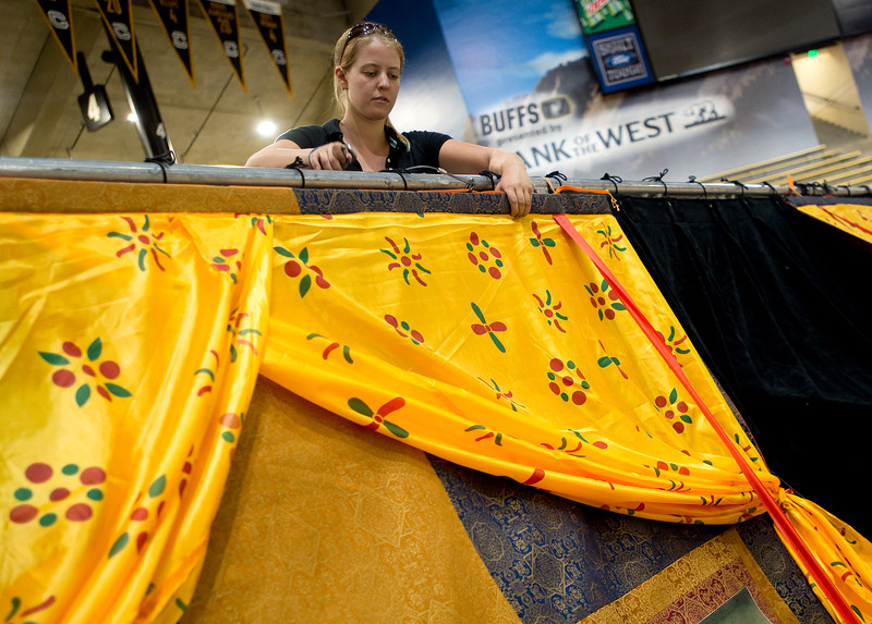 "Molly Goodman, with Rhino Staging, helps set up the backdrop at they prepare for the visit of the Dalai Lama in the Coors Event Center at CU Boulder on Wednesday.<br /> More photos:  <a href=""http://www.dailycamera.com"">http://www.dailycamera.com</a><br /> (Autumn Parry/Staff Photographer)<br /> June 22, 2016"