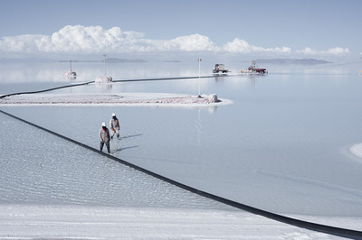 Two workers walking on the flooded surface at the lithium plant of Salar de Uyuni, Potosí, Bolivia.