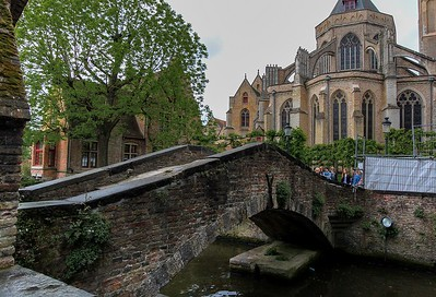 Old stone bridge in Bruges, Belgium.  What looks like a black X graffitti on the bridge is actually a very old decorative metal sculpture.