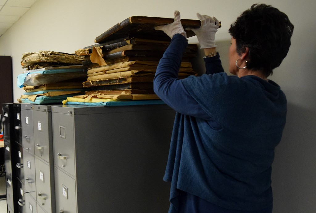 . Archives specialist Shirley Paquette carefully moves a historic, bound set of issues of The Oakland Press at the Kresge Library at Oakland University on Tuesday, Dec. 12, 2017.