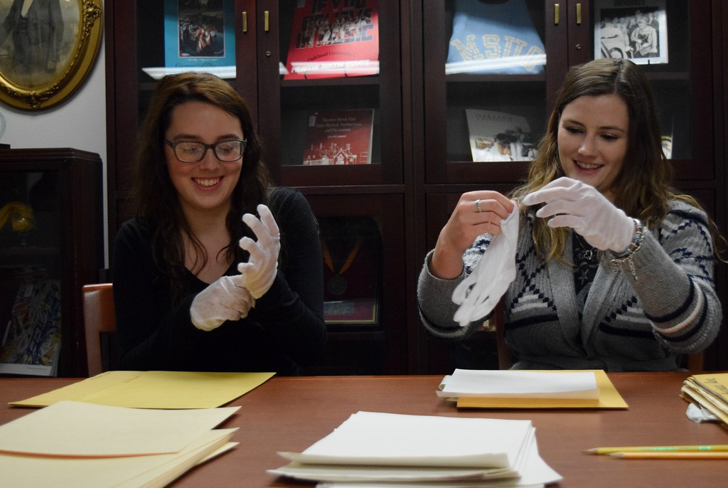 . Elizabeth Deneen (left), marketing major, and Lauren Spencer, first-year doctorate of physical therapy student, sort through historic photographs from The Oakland Press at the Kresge Library at Oakland University on Tuesday, Dec. 12, 2017.