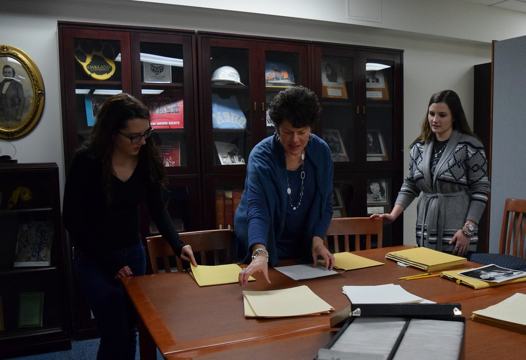 . Elizabeth Deneen (left), marketing major, stands with archives specialist Shirley Paquette and Lauren Spencer, first-year doctorate of physical therapy student, with historic photographs from The Oakland Press at the Kresge Library at Oakland University on Tuesday, Dec. 12, 2017.