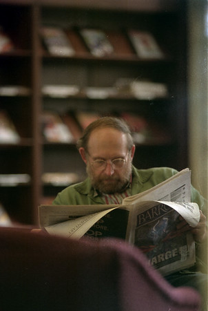 98/05/04 Rainy read2-Rachel Naber Photo-Ron Burg reads an article in Barrons at the Lockport Public Library as the rain perisits to fall outside.
