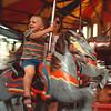 7/25/97--summer fest--Takaaki Iwabu photo-- Sam Hathaway, 2, Niagara Falls, was all smile as he ridedcarousel with his father Don Friday at Summer Festival in Niagara Falls. <br /> <br /> 1A, Saturday