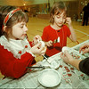 97/12/11 Christmas Bazaar - James Neiss Photo - L-R -  Alexandria Meranto 6yrs and Chelsea Holody 6yrs, both try their had a Christmas decoration making with the helping hands of Parent Volunteer Sara Ferrerio. This all took place at the G.J. Mann Elementary School Christmas Bazaar.