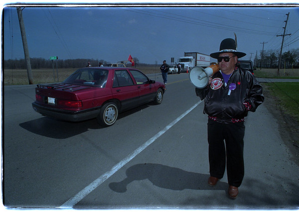 4/21/97 Tax Protest 2 - James Neiss Photo - Grandpa Bear, Ececutive director of the NY Chapter of the American Indian Movement. (905-994-0011) asks traffic to slow down at a informational stop on Rt. 31 at Chew Road. ( Some refured to the event as the Tuscarora Tea Party)