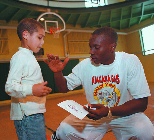 97/10/14--TIM WINN/YMCA--DAN CAPPELLAZZO PHOTO--ST BONA HOOPS STAR TIM WINN GIES FIVE TO A YOUNG FAN, 6-YR-OLD EMANUEL WILLIAMS DURING A BASKETBALL CLINIC AT THE YMCA.<br /> <br /> SP