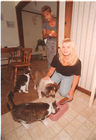 7/10/97 Safe and Snug - James Neiss Photo - Lee Ann Hurlburt, kneeling,  owner of Safe and Snug Petsitting Service takes care of Kathy Doel's (Standing left) cats,  Brat & Sugar and dog Micki.