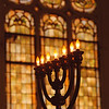 97/09/29--NF JEWISH COMMUNITY--DAN CAPPELLAZZO PHOTO--A Menura GLOWS BRIGHTLY IN FRONT OF STAIN GLASS AT THE TEMPLE BETHEL ON AHLAND AVE, NF.<br /> <br /> 1A