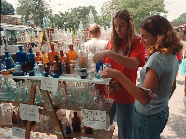 8/1/97 antique show 2--Takaaki Iwabu photo-- Terra Matthews, left, and Jen Conway, both 15, take a look at antique bottles placed on Center St in Lewiston Saturday. Fine Antique Show was part of Lewiston's AreFest '97. <br /> <br /> grapevine photo