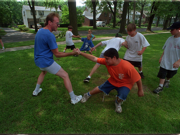 "7/2/97 Maple Ave. Playground - James Neiss Photo - Bob White, an instructor of ""Tracy's Kempo"" Martial arts works with Daniel Lounsbury 11yrs of Maple ave, and other Maple ave. playground visitors. White is a Karate Black Belst and aerobics instrtor teaching children the fundamental skills necessary to develop and imporve balance and cooordination.. See release..."