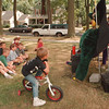 97/08/04--PUPPET SHOW--DAN CAPPELLAZZO PHOTO--5-YR-OLD JACOB CANNOVA WATCHES AND LISTENS FROM THE SEAT OF HIS BIKE AS VETERAN PUPPETREER JEAN STEWART ACTS OUT TRADITIONAL PUPPET THEATER AT THE MAPLE AVE. SCHOOL PLAYGROUND.<br /> <br /> LOCAL