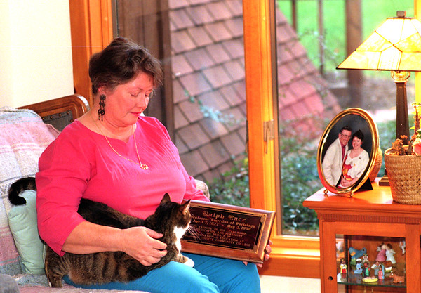 98/11/11 Susan Race *Dennis Stierer Photo -<br /> Susan Race sits in her sunroom with her cat 'Mittins'. On the table next to her is a photograph of her and her late husband as she holds a recent award given to him.