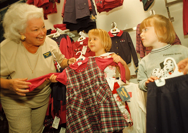 97/08/23-- Back to School 2--Takaaki Iwabu photo-- Pat Ward, store manager of OshKosh B'Gosh in Niagara Factory Outlet Mall, shows store items to Suzanne and Caroline Murphy Saturday. (For Eugene's back to school story..)