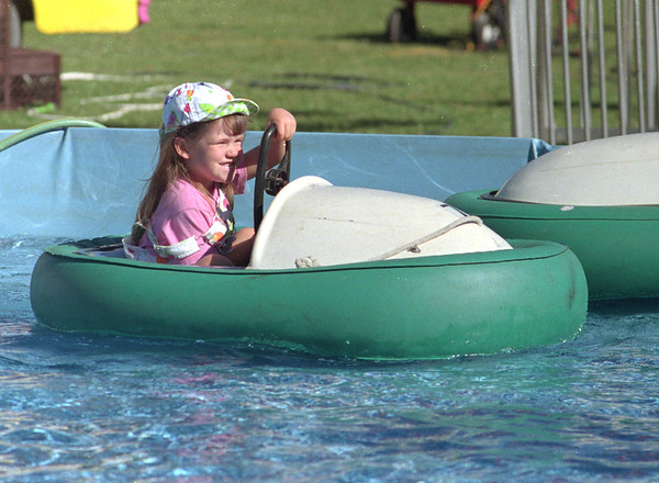 98/07/31 Dodge'm Boats *Dennis Stierer Photo - <br /> Elena Sirianni, 4  takes the helm as she bumps and bangs other boats in a giant swimming pool at the Shawnee Feild day Festival going on through Saturday.