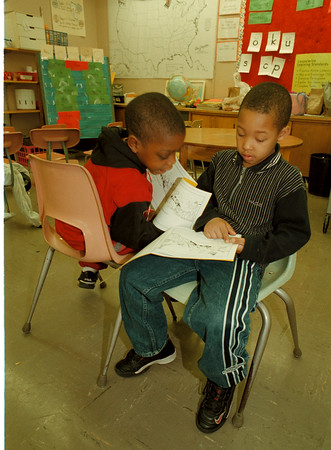 98/12/04 Reading Program - James Neiss Photo - L-R - Durelle Crittenden 6/1 and Nyle Marshall 6/1 buddy up to help to help each other read. Here, they are duscussing the correct pronunciation of a word.