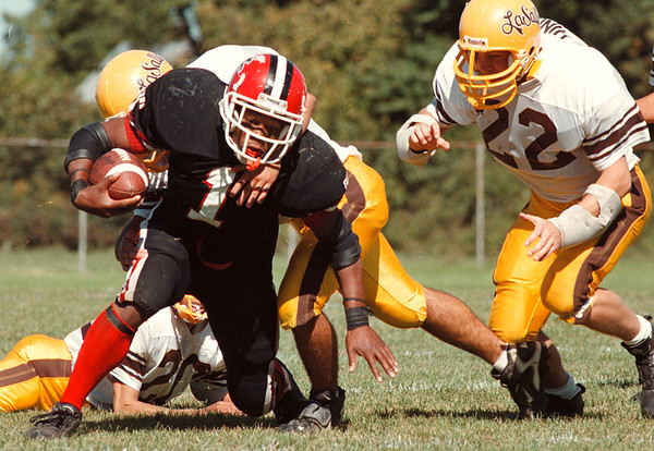 97/09/27 HS football--Takaaki Iwabu photo-- Niagara Wheatfield Rashad Evans tries to break away from LaSalle dfenders' tackle during the first half  (#22 is Joe Hinkle.) <br /> <br /> sports, Sunday, color