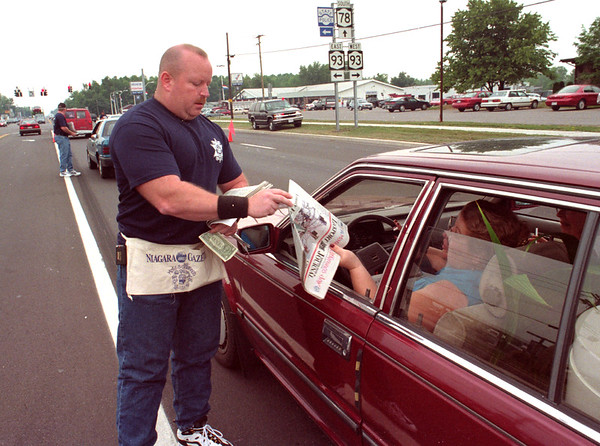 98/08/05--UNITEDWAY PAPER BOYS--DAN CAPPELLAZZO PHOTO--NIAGARA CO. SHERIFF OFFICER ROGER HUEBER, ALONG WITH FELLOW OFFICERS, PLAY PAPERBOY FOR A DAY SELLING COIES OF THE US&J AT THE CONER OF 78 AND ROBINSON RD TO BENEFIT THE UN.