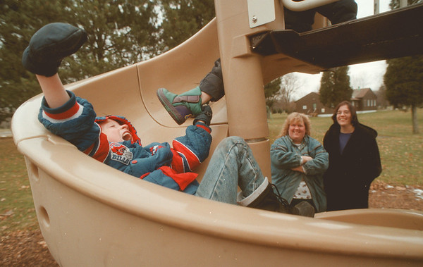 98/01/02 Slide Fun - James Neiss Photo - Adam McNallie 6yrs of Wilson, is all smiles as he enjoys the unseasonable warm temps wile sliding at Old Fort Niagara State Park. Up top is friend Lee Oiler of Porter. Mom's L-R, Peggy Oiler and Marcia McNallie.