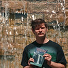 5/15/97--WATERFALL BOY--DAN CAPPELLAZZO PHOTO--SCOTT ENSMINGER, OF NT, PROUDLY DISPLAYS HIS BOOK ON THE NUMEROUS WATERFALLS AT LETCHWORTH STATE PK, WHILE SITTING IN FRONT OF THE MANMADE WATERFALL AT THE N.T. LIBRARY.<br /> <br /> FEATURE TUES