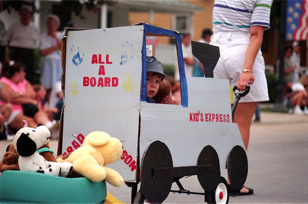 "98/08/15 Kid Parade2-Rachel Naber Photo-Brad Duhow, age  3 rides down Main Street with his sister Allison, 9 months  in a card board cut out train named ""Kids Express"" as part of the Newfane Kids parade."