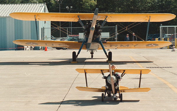 """97/09/21--NF AIRSHOW--DAN CAPPELLAZZO PHOTO--6-YR-OLD GINO LoBIANCO, OF N.F., FLIES WITH THE BIG BOYS AS HE PEDDLES HIS """"1929 FLEET"""" TOY PLANE IN FRONT OF 1937 STEARMAN VINTAGE AIRPLANE ON THE TARMACK AT THE NF AIRPORTS' ANTIQUE AIRSHOW.<br /> <br /> LOCAL"""