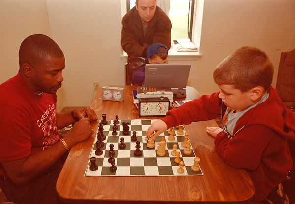 97/09/29--CHESS CLUB--DAN CAPPELLAZZO PHOTO--(LTOR) CHESS CLUB PRES. JAMES WARE PLAYS A GAME OF SPEED CHESS WITH 7-YR-OLD JOHN GROSSMAN AS JOHN HEROWSKI LOOKS OVER THE SHOULDER OF 5-YR-OLD TIM GROSSMAN DURING A MATCH ON THE COMPUTER.<br /> <br /> ECHO