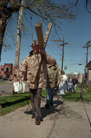 98/04/10 Cros Walk 1-Rachel Naber Photo-Roger Nelson carries the cross down Heritage Court and Pine followed by fellow parishners in Lockport.