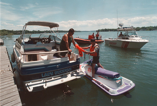 7/11/97 Boat Inspections - James Neiss Photo - Fort Niagara public Docks - Niagara County Marine Deputy David Gombert, Right, checks a life vest for safety with the cooperation of boater Walter Crawford of Youngstown. The Niagara County Sheriff Dpt and US Coast Guard will be conducting safety inspections.