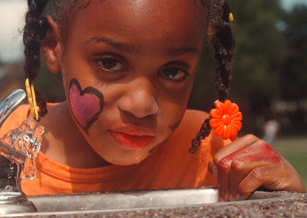 97/08/30 --love & peace-- Takaaki Iwabu photo-- A 5-year-old N'dea Frank gets some water at Gluck Park Saturday during the Gluck Park Gospel Festival. Area's children joined the Festival for music, food and face painting. <br /> <br /> grapevine photo