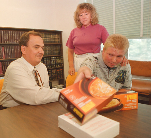 8/12/97-P.K.U /MAZIARZ BILL--DAN CAPPELLAZZO PHOTO--12-YR-OLD CHIRSTOPHER DeLONG REACHES FOR THE SPECIAL FOOD THAT HE NEEDS TO EAT DUE TO HIS PKU DISEASE. HIS MOTHER ARLENE AND STATE SENETOR GORGE MAZIARZ LOOK ON AT NIAGARA COUNT COURT BLDG. MAZIARZ HAS A BILL TO HELP WITH FOOD FOR POEPLE WITH THIS PROBLEM.<br /> <br /> 1A