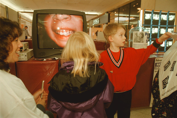 98/02/21-- dental week --Takaaki Iwabu photo-- Casey Lang, 5, right, shows a picture of his teeth to her mother as his sister Jillian, middle, faces to the television  monitor. Demonstration of the intra-oral camera was one of the activities at the 4th annual Children's Dental Health Fair at Summit Park Mall.     -- BW, Sunday, local