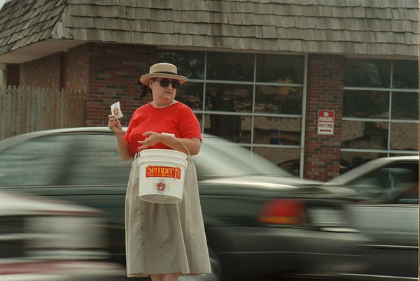 98/30/08 Daring Donation-Rachel Naber Photo-Gail Borycki collects donations for the U.S. Marine Corps Monument as she stands in between on coming traffic on Military Road.