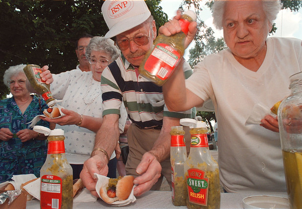97/08/07-- Senior Picnic-- Takaaki Iwabu photo-- Walter Bennette, middle, and other participants of Senior Citizen Picnic put a final touch on their hot dogs with relish. About 150 locals gathered for the 4th Annual picnic at Senior Citizen Park Thursday. <br /> <br /> Grapevine photo
