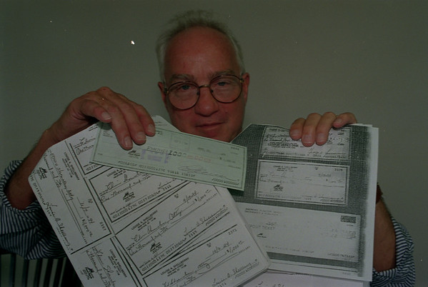 98/10/07 Albright Checks - James Neiss Photo - Attorney Robert S. roberson holds up checks involved in scandle.