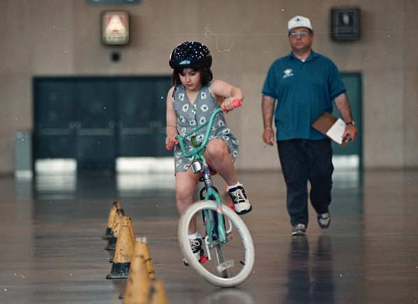 5/27/97--bike rodeo--DAN CAPPELLAZZO PHOTO--8-YR-OLD SAMANTHA GUYETTE, OF HYDE PARK SCHOOL NAVIGATES THE PYLONS AS BIKE RODEO VOLUNTEER ART BRIGLIO LOOKS ON AT THE NFCC.<br /> <br /> LOCAL