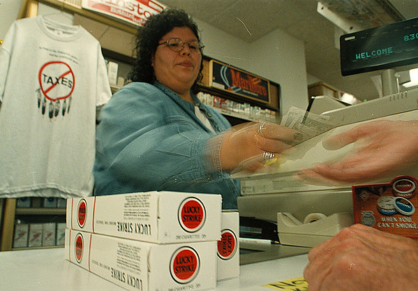 4/16/97-- Jay's Place-- Takaaki Iwabu photo-- Lynette Jamieson, casher at Jay's Place in Tuscarora Nation, hands out the change to a customer who buys cartons of cigarette. (pic for Val's story on some license regulation on stores in Indian Nation) <br /> <br /> 1A, Thursday